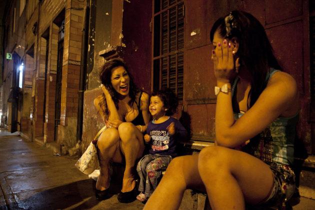 Duas mulheres conversam com garotinha na rua