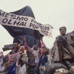 """A foto mostra a escultura """"Cristo Mendigo"""" que foi o carro abre-alas do desfile Ratos e Urubus. Na imagem, a escultura é coberta por sacos de lixo como uma censura, e carrega a faixa que diz """"Mesmo proibido olhai por nós!"""""""