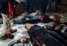 """A foto mostra protestantes performance um """"Die in"""". A manifestação é contra a família Sackler, ligado à Purdue Pharma, produtora do Oxy Contin. Em meio aos protestantes está a fotógrafa Nan Goldin, rodeada por papéis que dizem """"Sackler Lie People Die"""" e frascos de remédio"""