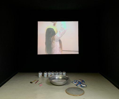 """Peça da exposição Ratos e Urubus - A foto mostra a exibição de uma gravação da performance """"Pancake"""" de Márcia X. Abaixo do telão onde é projetado o vídeo estão objetos equivalentes aos usados por ela na sua performance."""