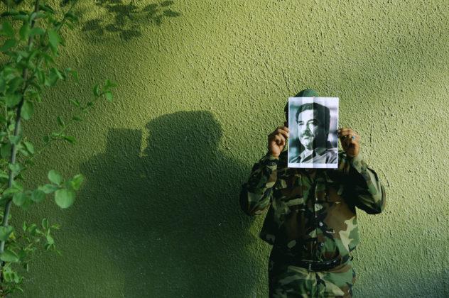 """Na foto, trabalho da série """"Saddam is Here"""" de Jamal Peniweny, vemos um homem, posicionado contra uma parede verde, vestido com roupas militares que segura uma foto impressa em papel comum de Saddam Hussein"""