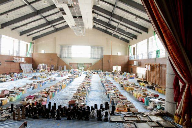 Na foto, vemos o ginásio de uma escola, na parte mais ao sul da prefeitura de Miyagi, repleto com caixas de fotografias e outros pertences resgatados pelo SDF