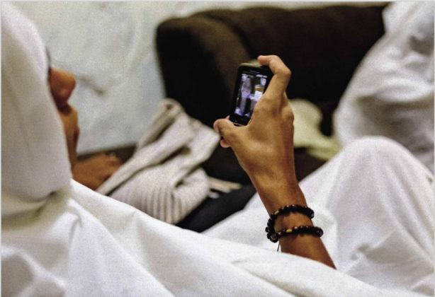 Jovem penitente vestida com roupa ritualística branca checa seu celular