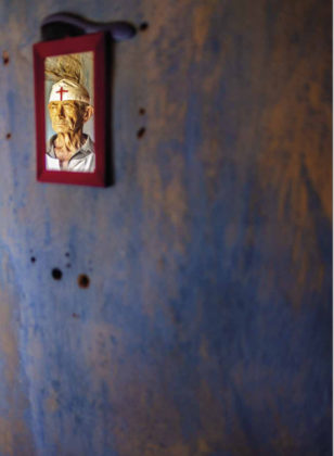 A foto mostra o reflexo do Sr. José Carneiro de Aquino, um dos penitentes, em um espelho com bordas vermelhas pendurado em uma parede azul já desbotada