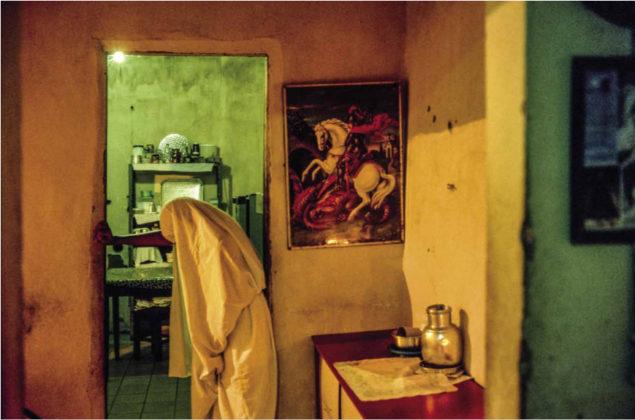 Na foto uma das penitentes, já com roupa ritualística branca, se apoia contra parede - onde seria colocada uma porta - para realizar uma prece, atrás dela está um quadro de São Jorge lutando contra o dragão