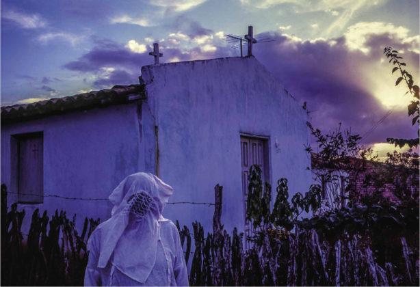 Na foto vemos o Sr. Juvenal Pereira de Andrade vestindo indumentária completa em frente a uma capela construída por ele mesmo