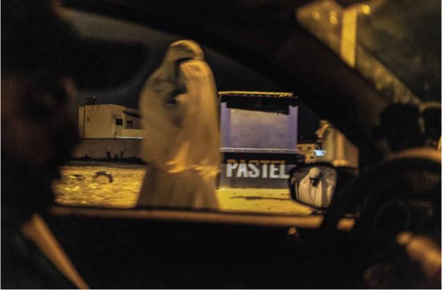 """Na foto vemos uma das Alimentadeiras de Almas vestindo indumentária branca, a vemos pela janela de um carro, no reflexo do espelho do carro é possível encontrar uma segunda Alimentadeira. Atrás da primeira está uma banca azul escrito """"pastel"""""""