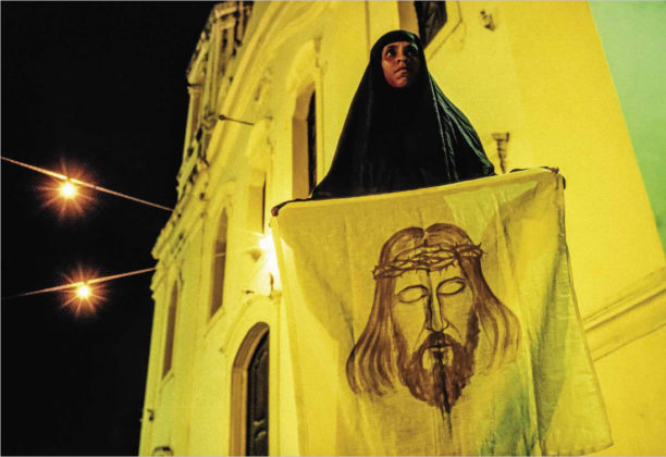 Penitente inteira coberta de preto carrega um simulacro ao Manto de Verônica