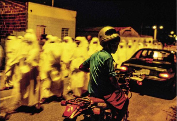 Menino em motocicleta passa pelos penitentes durante procissão