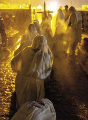 Penitentes rezam de joelhos debaixo de chuva torrencial