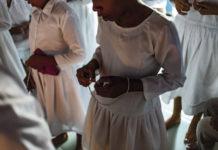 Meninas e mulheres vestindo hábitos claros rezam ave-marias com terços nas mãos