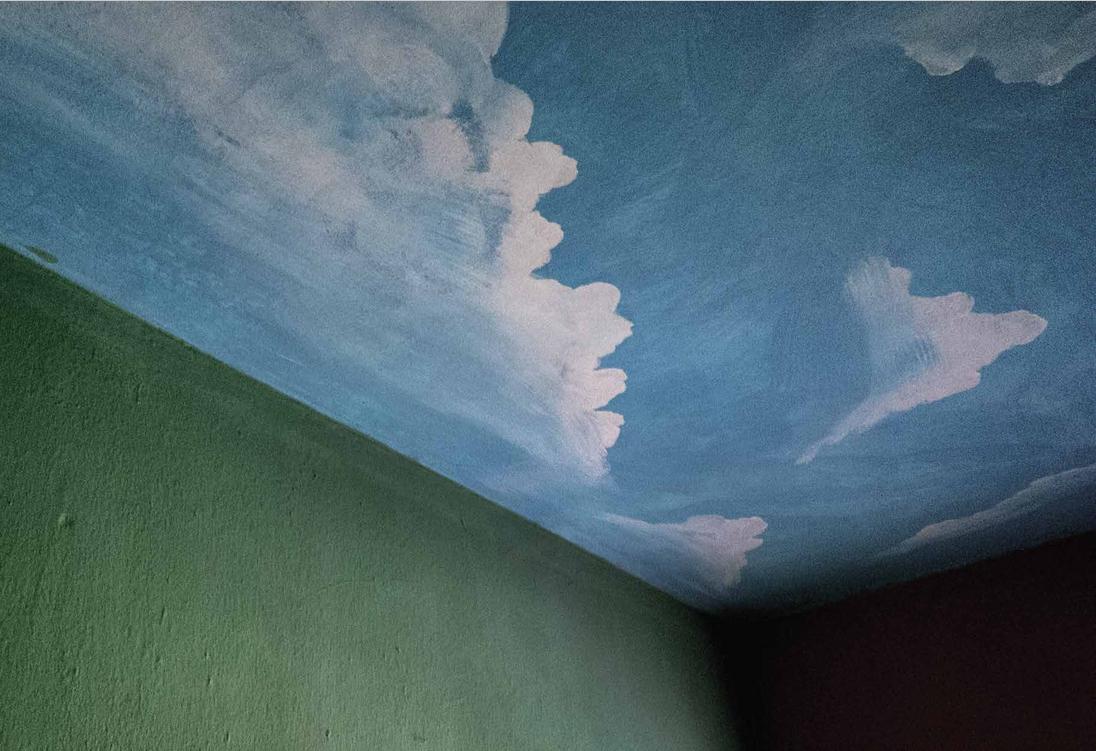 A foto mostra o teto de um quarto de hotel, em Carmópolis, pintado como se fosse o céu