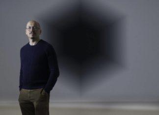 """Iran do Espírito Santo em frente à sua obra """"Recuo Hexagonal"""" (2006)."""