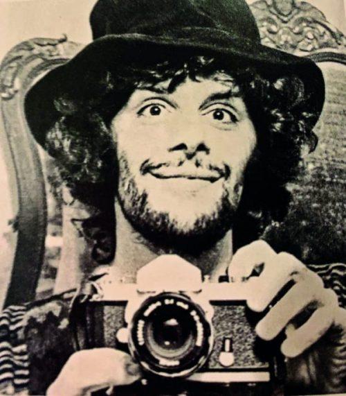Autorretrato de Aguilar tirado frente a um espelho, está com a câmera nas mãos e sorrindo.