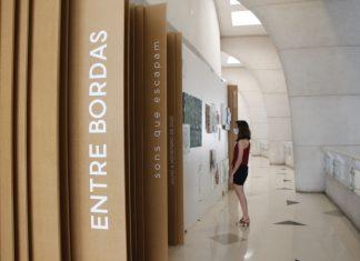 """No primeiro plano, divisões de madeira na parede tem o escrito """"Entre Bordas"""", na vertical. Ao fundo, uma mulher olha quadros da exposição """"Entre bordas - sons que escapam"""" na parede"""