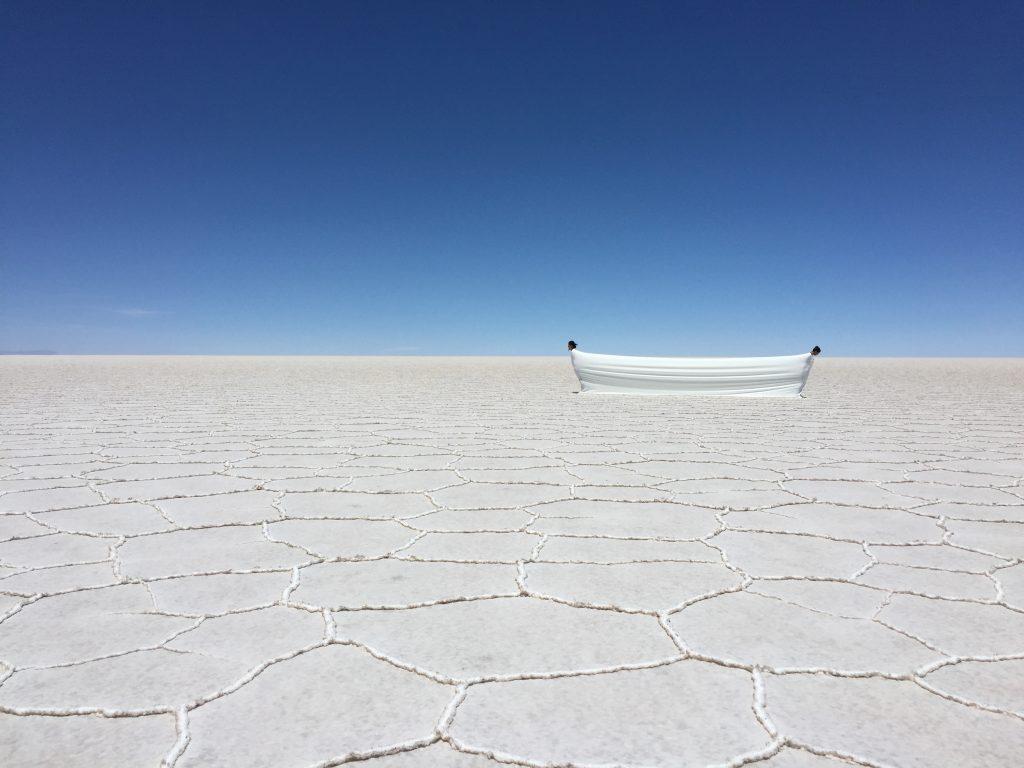 """A imagem mostra a obra """"Estudo para o Tempo Suspenso Ma 間 :: Silêncio, o espaço tempo de resistência e resiliência"""", de Dudu Tsuda, onde duas pessoas se equilibram envolvidas por um mesmo tecido, no deserto de sal 'Salar del Uyuni' para IX Biennal SIART de La Paz"""
