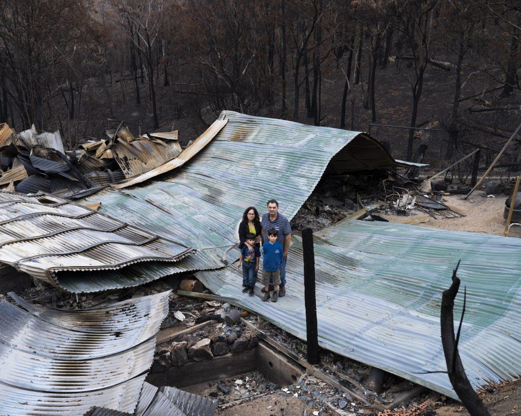 Gideon Mendel, série Fire, Anthony Montagner com sua família, sua esposa Fina e seus filhos Christian (9) e Dylan (6), onde costumava ser seu lar, agora completamente derrubado pelas chamas. Upper Brogo, Austrália, 18 de janeiro de 2020.