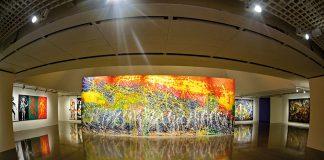 """Pintura horizontal """"Rio Amazonas"""", de Aguilar, em meio à uma sala de exposição."""