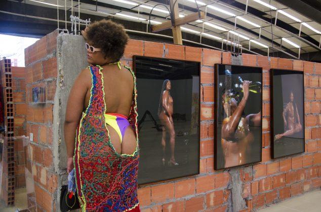 A artista multidisciplinar Ventura Profana ao lado de sua exposição na Mostra 2020 do CCSP. Foto: Artur Cunha/CCSP