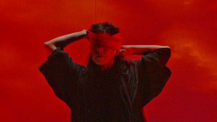 A performer Emilie Sugai está no centro da foto, vendando seus próprios olhos com uma faixa vermelha. A iluminação da imagem é toda vermelha, contextualizando um dos momentos do espetáuculo AKA
