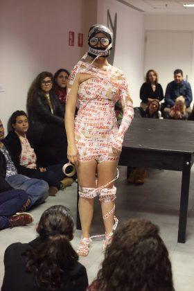 Fotografia vertical, colorida. Estela Lapponi está de pé no centro. O público, majoritariamente formado por mulheres está sentado em torno dela e a olha. Ela tem o corpo enfaixado da púbis até a cabeça com uma fita adesiva branca com escrito FRÁGIL em vermelho. Na cabeça, uma touca preta e os óculos Zuleika Brit, que possui olhos desenhados. Essa foto foi tirada pelo fotógrafo Ivson Miranda durante a performance INTENTO 00035 - ÇA M'ÉNERVE!!! do projeto Corpo Intruso apresentada no Itaú Cultural.