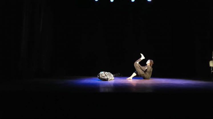 Foto horizontal, colorida. João Paulo Lima aparece em distância, ele está sentado sobre o palco, de perfil para a câmera. Sua perna direita está flexionada, com o pé apoiado no chão. A prótese da perna esquerda está encaixada ao corpo do lado contrário, fazendo com que o joelho e os dedos do pé não estejam na frente do corpo, mas alinhados às costas. Ele ergue a prótese do chão com uma das mãos, flexionando o joelho da mesma e levando o pé em direção ao rosto, o que deixa explícito o encaixe incomum da prótese. Ele usa um figurino todo preto e uma máscara branca no rosto. A imagem mostra o palco por completo. O ambiente está escuro e um refletor foca no artista, fazendo com que apenas essa cena fique iluminada e apareça na fotografia. A imagem é um still do espetáculo NOTRO CORPO.