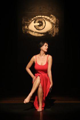 Foto vertical, colorida. Moira Braga está no palco sentada em uma cadeira de frente para nós, com as pernas cruzadas em uma pose sensual. O rosto está virado para a nossa direita, fazendo com que ela fique de perfil para o público. Tem uma expressão calma e contemplativa. Moira usa um vestido vermelho e longo de alças, a barra do mesmo está apoiada sobre um dos joelhos, deixando suas pernas expostas ao público. Acima de sua cabeça, pintado na parede, há o desenho realista de um olho em tons de cinza. O palco está escuro e um refletor foca na artista e no desenho, fazendo com que tudo ao seu redor fique escuro e apenas essa cena iluminada. Essa foto foi tirada por Janderson Pires durante a peça teatral VOLÚPIA DA CEGUEIRA.