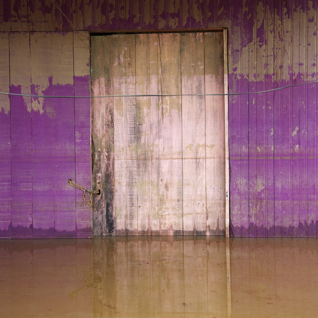 """From the """"Floodlines"""" series: Mendel registers the mark left by the increase in the water level at the entrance to a house in the district of Taquari. Rio Branco, Brazil, March 2015."""