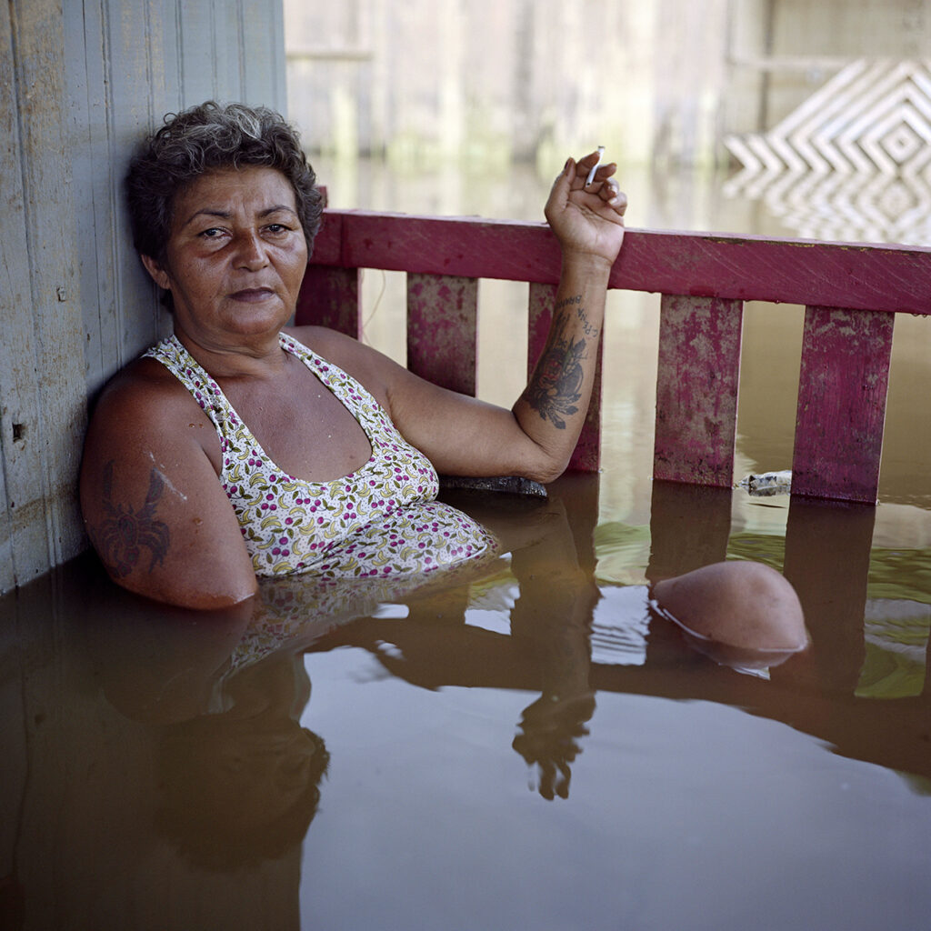 """From """"Submerged Portraits"""" by Gideon Mendel: """"It often floods here, almost every year, so most of our homes are on stilts. But nobody can remember a higher flood. We are all camping now. We have no choice but to be in the water, even though the snakes make it dangerous. I've heard the government has plans to move us away and turn this area into a park. But I've heard this for years and we are still here. It's not a big deal: when the floods come, we take our stuff and leave for a while"""". Francisca Chagas dos Santos, Rio Branco, Brazil, 10 March 2015."""