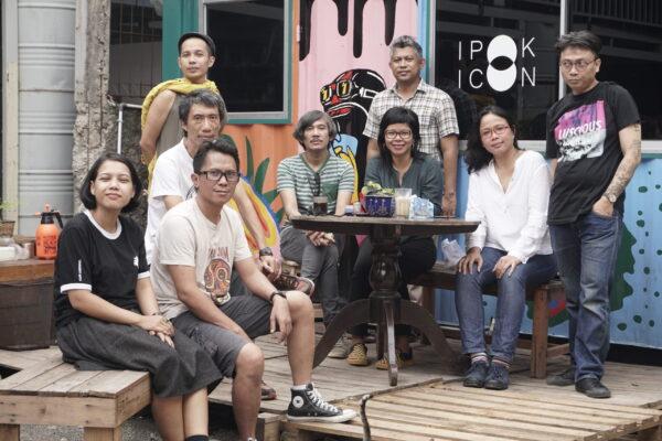 Foto horizontal, colorida. Nove membros do coletivo de artistas ruangrupa reunidos