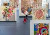 Foto horizontal, colorida. Em meio à exposição BEATRIZ MILHAZES - AVENIDA PAULISTA, dois bailarinos dançam. Ele usa uma camisa branca e uma calça preta. Ela usa um vestido vermelho de mangas longas. Ambos estão descalços. A performance é parte da programação da PAULISTA CULTURAL.