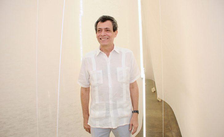 Foto horizontal, colorida. Carlito Carvalhosa está de pé, usa uma camisa branca de mangas curtas e uma calça cinza claro. Sorri. Ao fundo, a Instalação FAÇO TUDO PARA NÃO FAZER NADA.