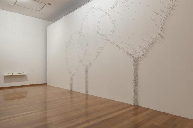 Foto horizontal, colorida. Obra PAISAGEM CRESCENDO na exposição MOTO-CONTÍNUO. Centenas de cigarros que parecem pontos da parede criam imagens de árvores.