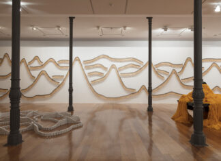 Foto horizontal, colorida. Vista da exposição MOTO-CONTÍNUO, de José Damasceno, na Estação Pinacoteca. Ao fundo, TRILHA SONORA, que com centenas de martelos pendurados em pregos na parede, cria a representação de montanhas. A frente, diversas colunas de estrutura do edifício. Entre elas, vê-se parcialmente duas obras de José Damasceno. À direita, SNOOKER, a esquerda obra mais baixa, no nível do chão.