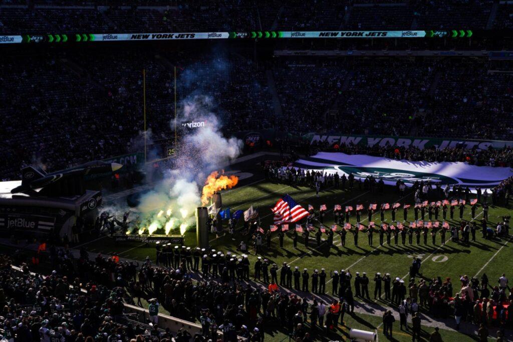 """""""Novembro é o mês de Saudação ao Serviço na Liga Nacional de Futebol (NFL). Ela surgiu de uma iniciativa do Pentágono para aumentar o recrutamento e, desde 2009, o Pentágono deu pelo menos $12,2 milhões para a NFL para propaganda. O senador John McCain conduziu uma investigação sobre a prática e divulgou esta declaração com um relatório detalhado de suas descobertas: """"Os americanos deveriam estar profundamente desapontados com o fato de muitas das cerimônias de homenagem às tropas em eventos esportivos profissionais não estarem realmente sendo conduzidas por um senso de patriotismo, mas para lucro na forma de milhões em dólares do contribuinte, que vão do Departamento de Defesa para ricas franquias de esporte"""". EUA. 2018   Crédito: Peter van Agtmael/Magnum Photos. Cortesia do fotógrafo."""