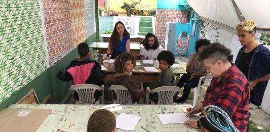 Imagem horizontal colorida. Um coletivo de artistas sentados em torno de duas mesas no ateliê do JAMAC conversam. Algumas folhas de papel sobre as mesas.