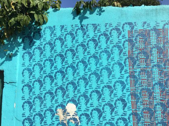 Foto horizontal, colorida. Uma parede azul com dezenas de impressões de estêncil do rosto de Marielle Franco, em um tom mais escuro de azul. Esta é uma das paredes de entrada do JAMAC.