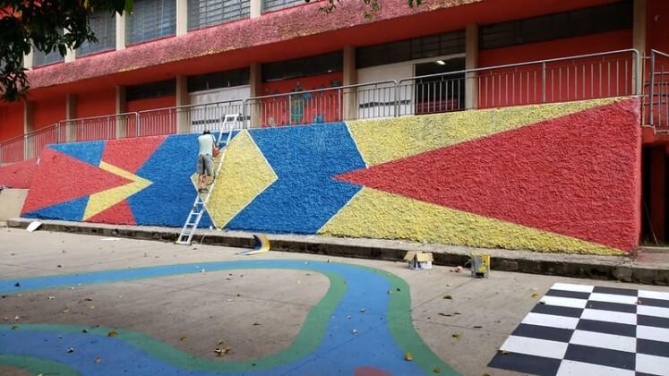 Foto horizontal, colorida. Coletivo Cicloartivo na EMEF Campos Salles criando um mural colorido e geométrico em uma das paredes da escola. A internvenção é parte do projeto Escola Criativa do Instituto Choque Cultural