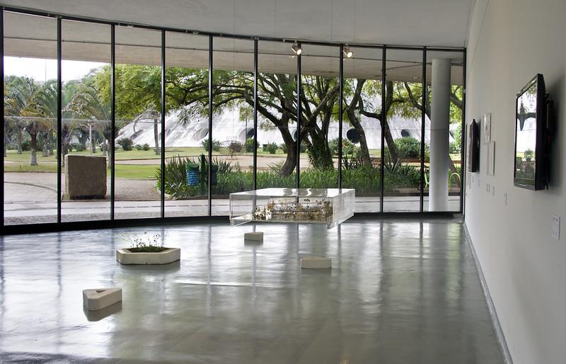 Foto horizintal, colorida. Vista da exposição ZONA DA MATA no MAM São Paulo. Em primeiro plano, uma obra em um aquário de vidro suspenso e um pequeno canteiro no chão, em formato de pentágono. Ao fundo, as paredes de vidro do espaço expositivo trazem o ambiente do Ibirapuera para imagem, é possível ver vegetação e a Oca ao fundo.