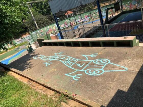Foto horizontal, colorida. Chão de cimento de uma escola pública de São Paulo traz um trabalho do artista urbano TEC em azul, O desenho é lagarto, em tom de azul claro, formando com seu corpo atípica brincadeira amarelinha. A obra é parte do projeto Escola Criativa do Instituto Choque Cultural.