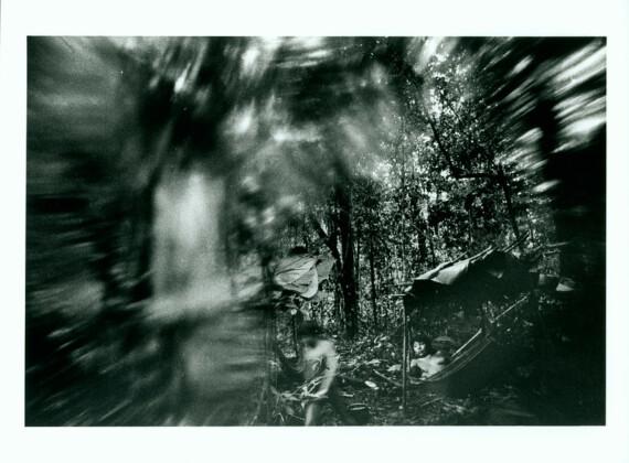 Foto horizontal, tons de cinza levemente esverdeado. Fotografia da série A FLORESTA, de Claudia Andujar, mostr duas pessoas da etnia Yanomami em meio à floresta. O homem está sentado e uma rede, no quadrante esquerdo inferior da imagem. No quadrante central inferior, uma mulher caminha. A fotografia tem uma área desfocada, que cria um meio círculo em torno dos dois personagens, dando foco a eles. A obra faz parte da exposição ZONA DA MATA no MAC USP